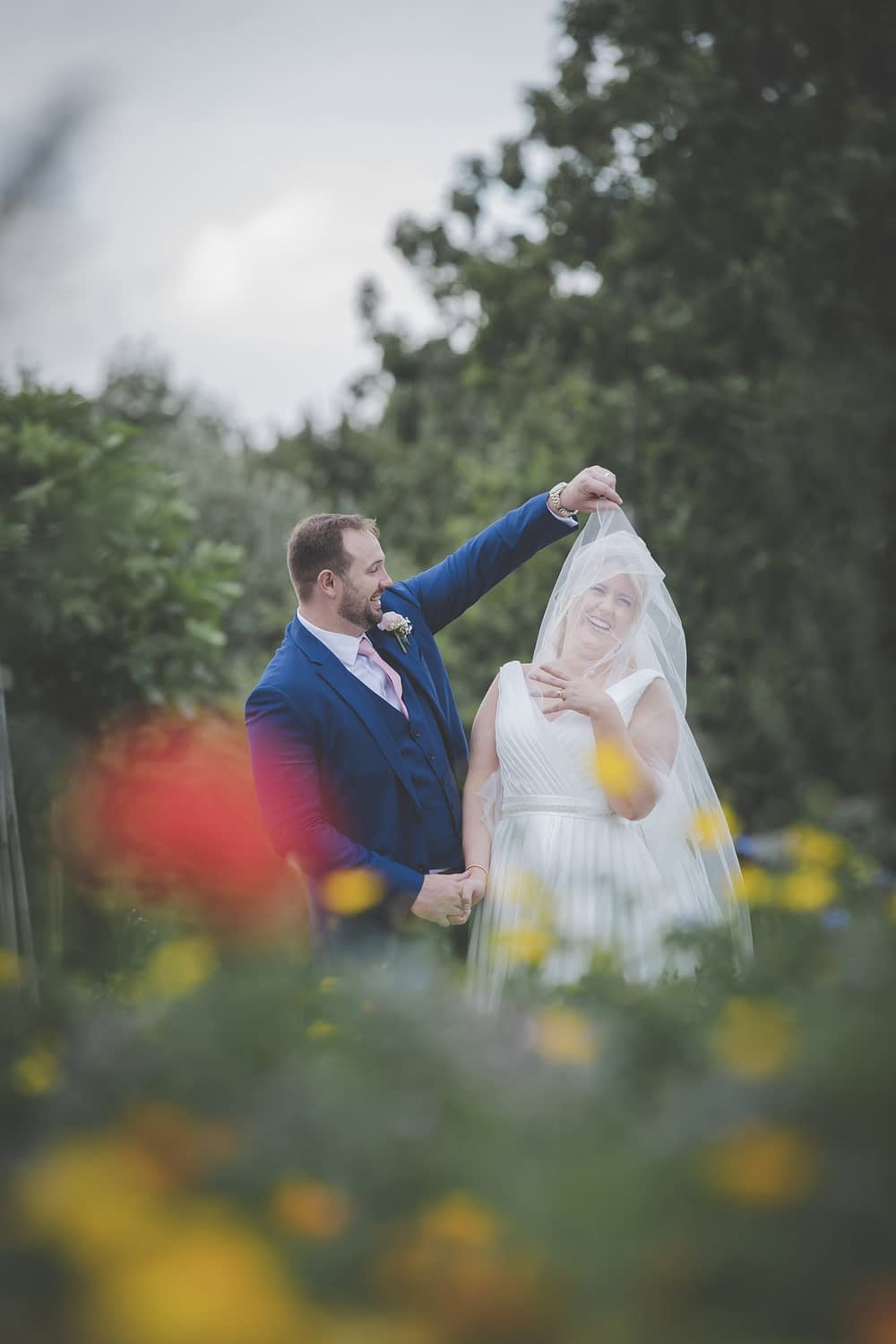 couple standing together with veil blowing in the air