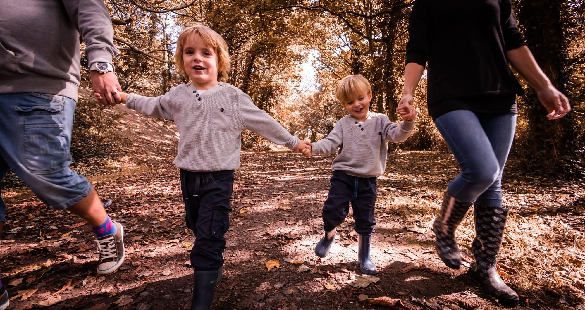 family walking through autumn leaves
