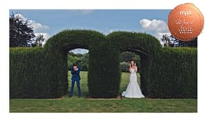 bride and groom laughing in front of a hedge