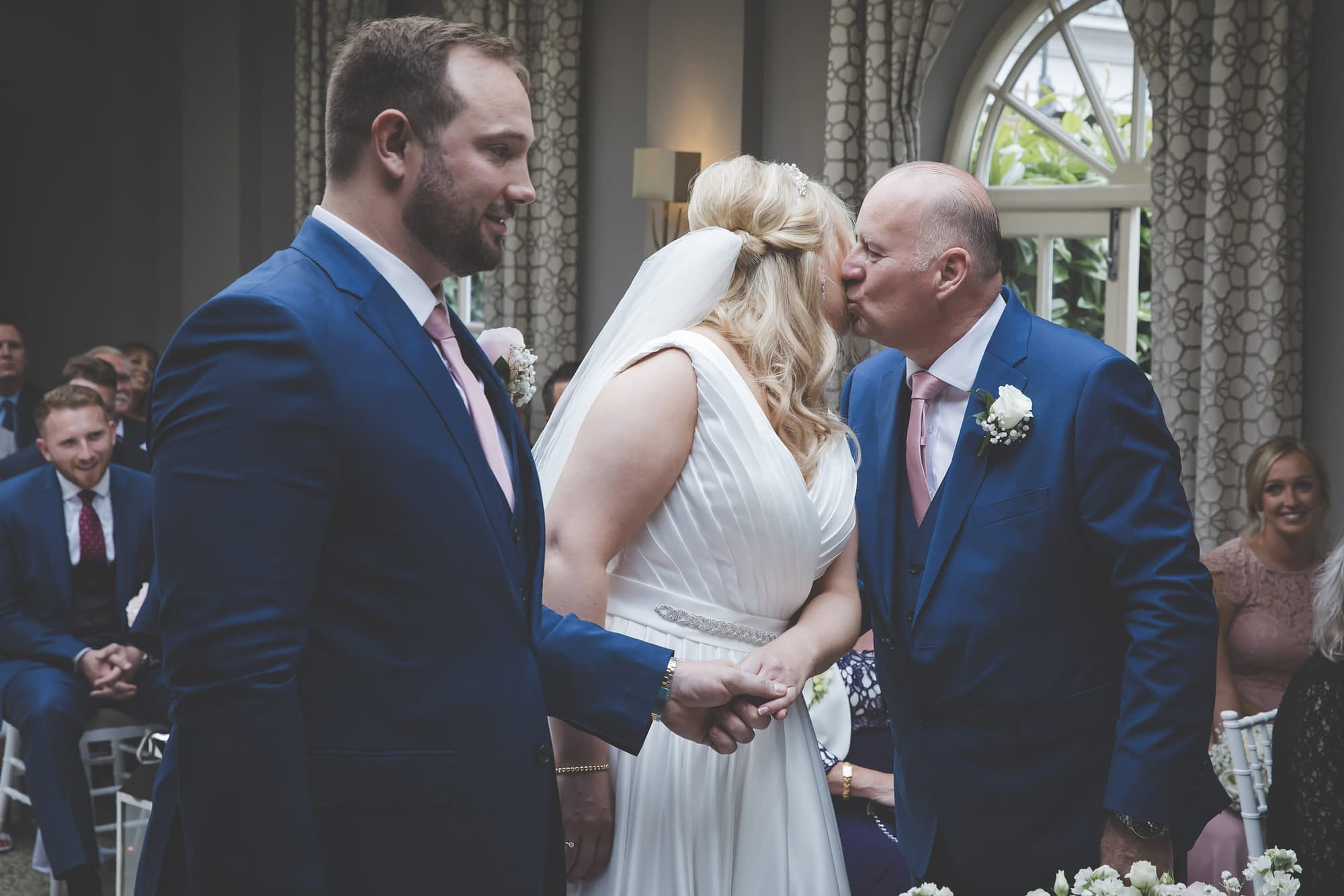 dad gives bride a kiss on the cheek