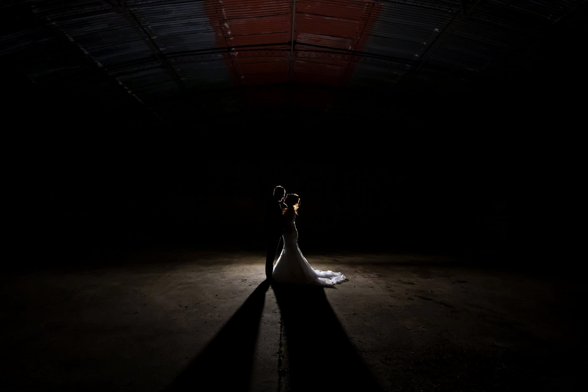 couple standing together in derelict barn at night