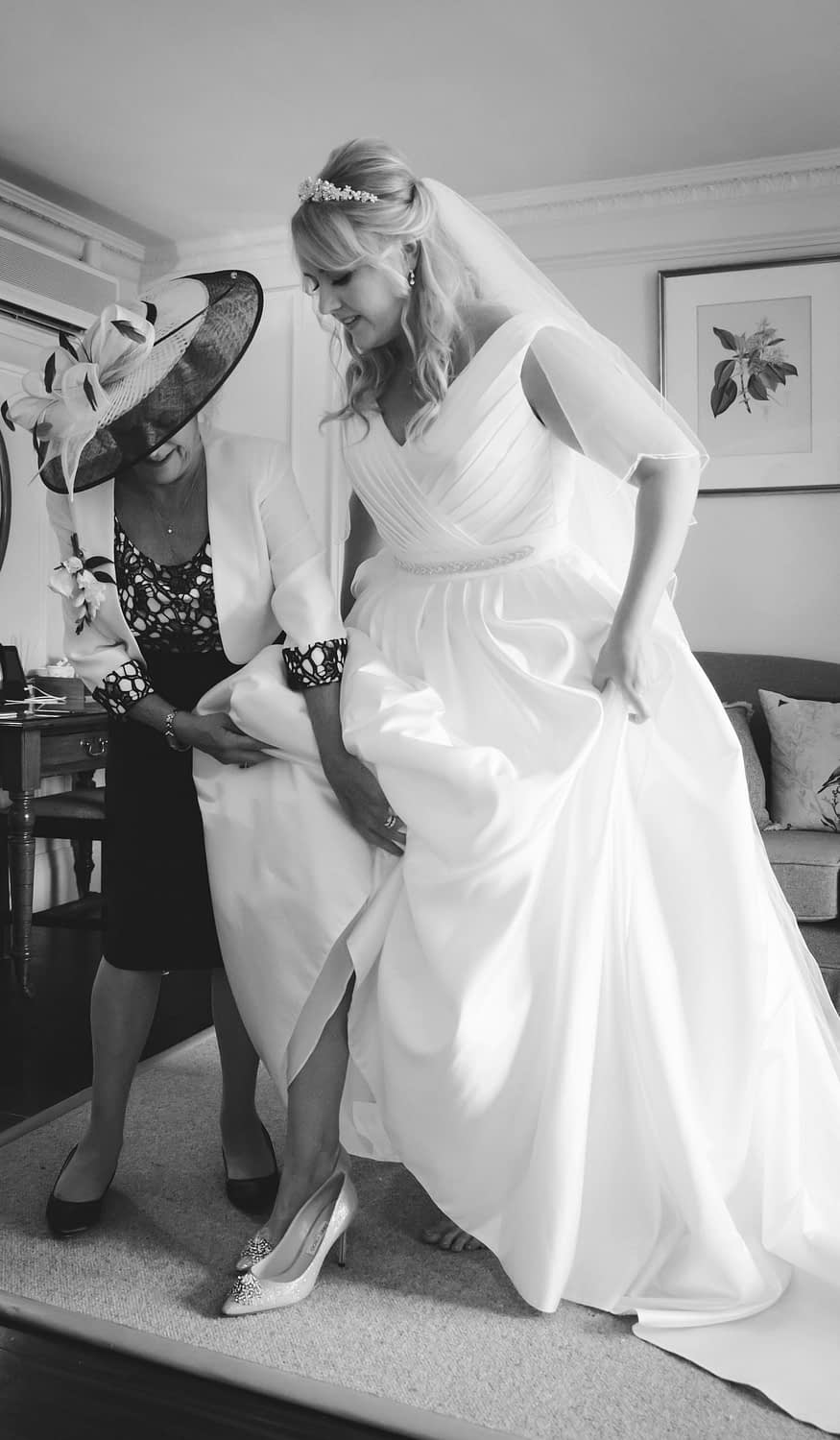 mum helping bride into her shoes