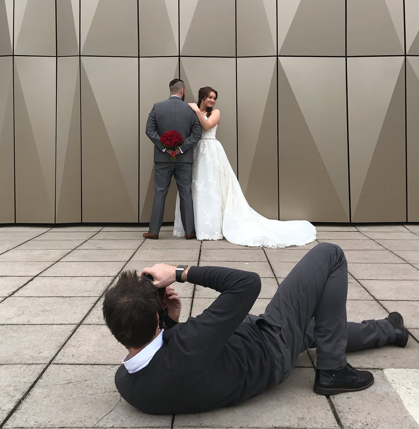 photographer laying down photographing wedding couple