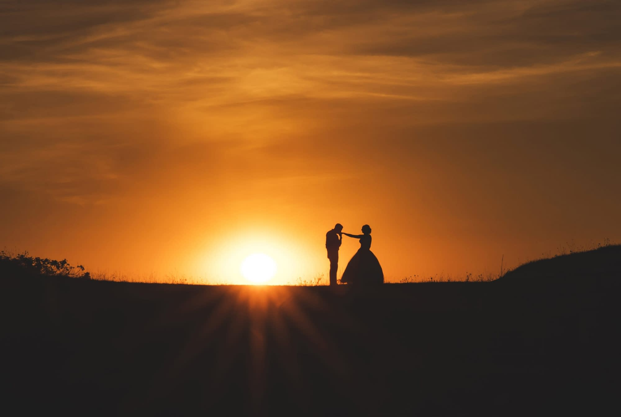 couple standing on a hill with sunset behind them
