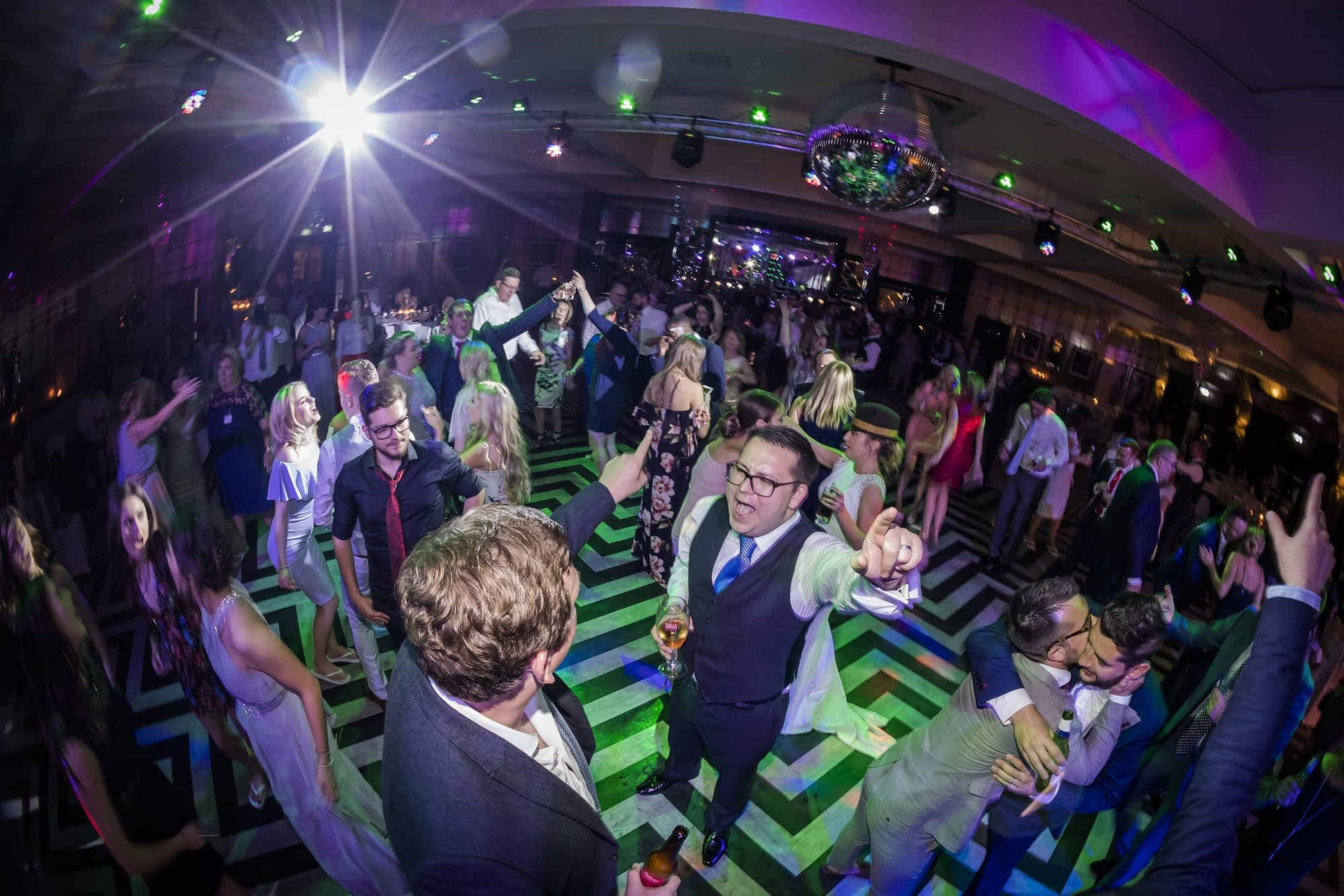 group of wedding guests dancing with coloured lights