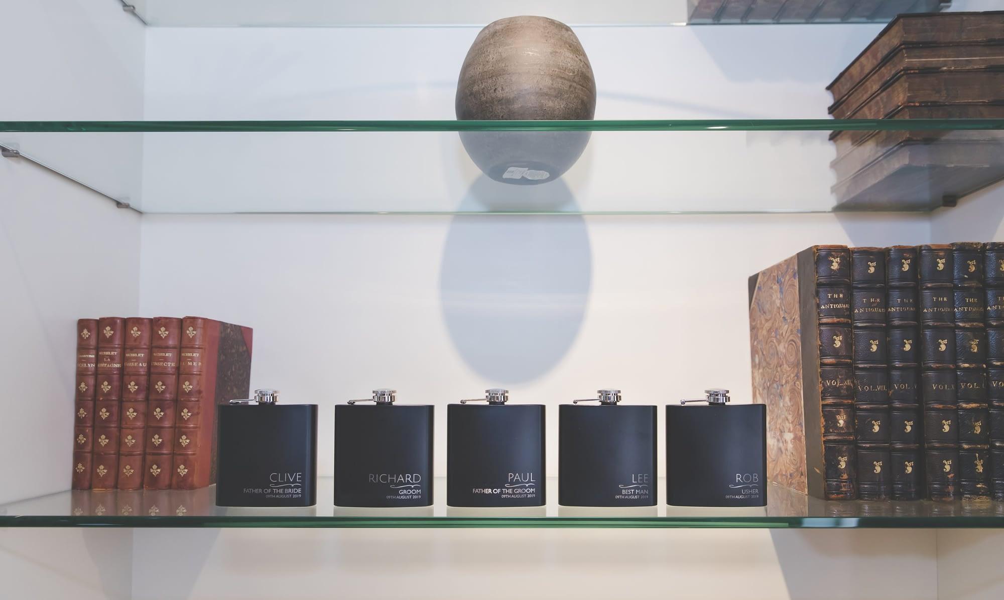 5 hip flasks on a glass shelf with books