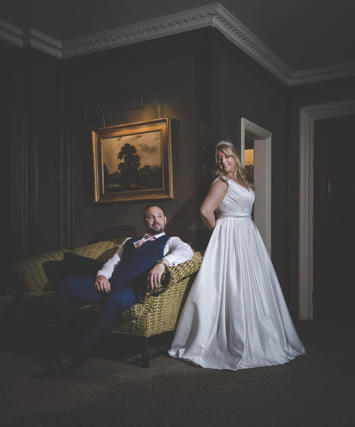 groom sitting on sofa whilst bride leans against the wall