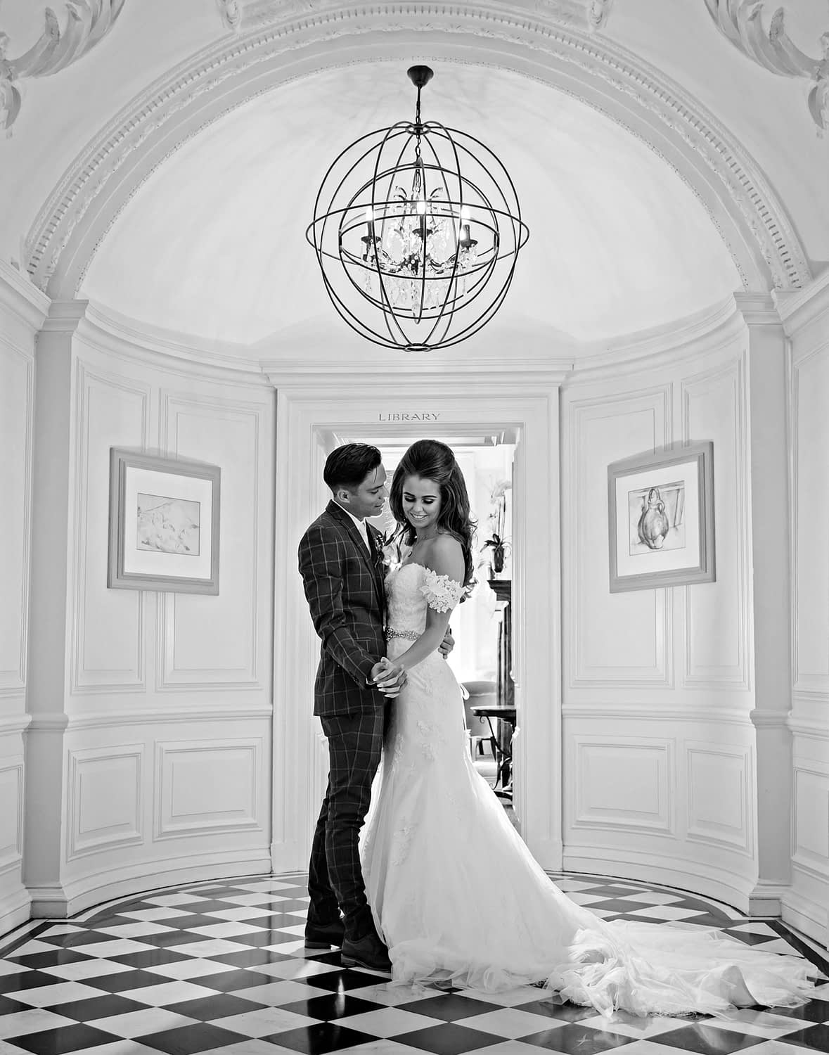 bride and groom stand together in Manor House corridor