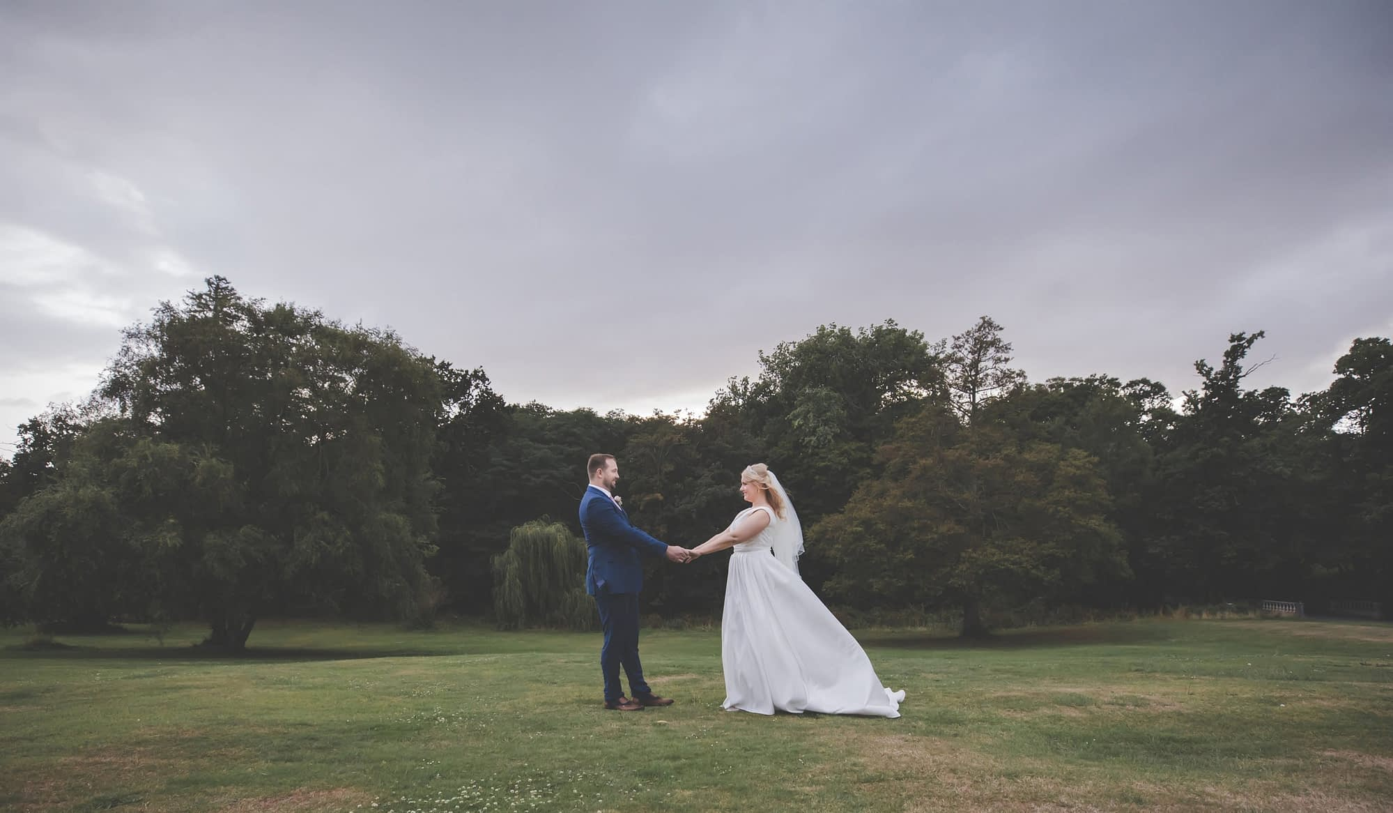 couple standing together outside with trees in the background