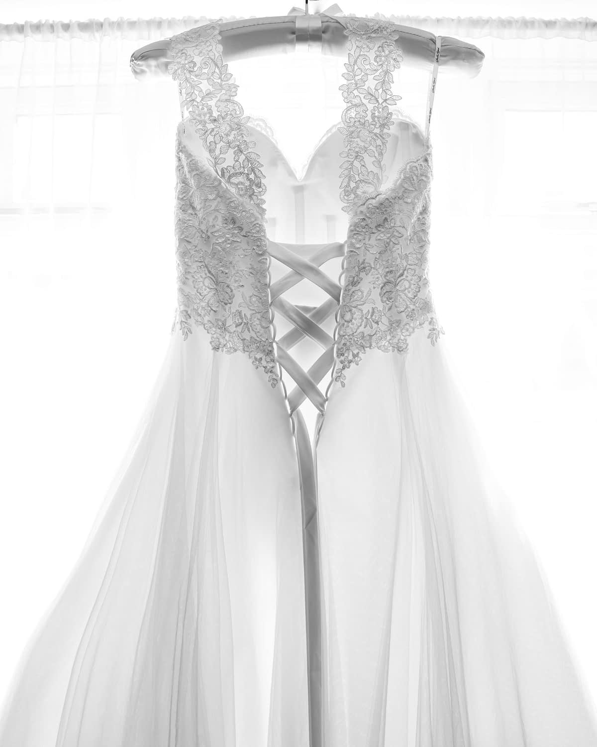 bridal gown hanging up in front of window