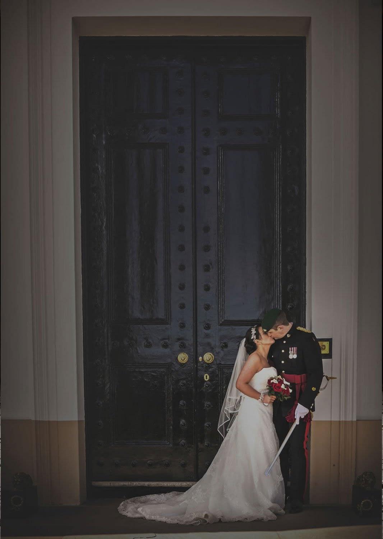 groom in army uniform kissing bride in front of big doors