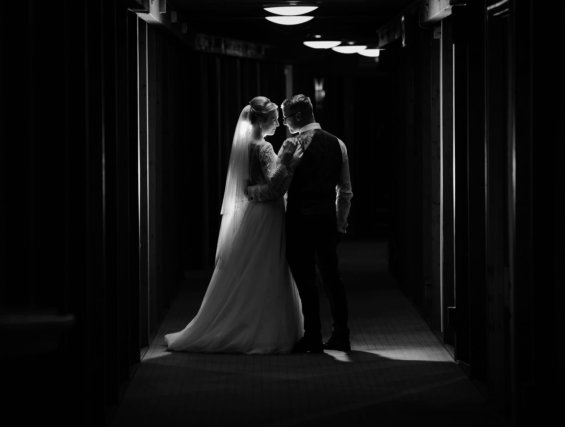 couple standing together at night in hotel corridor