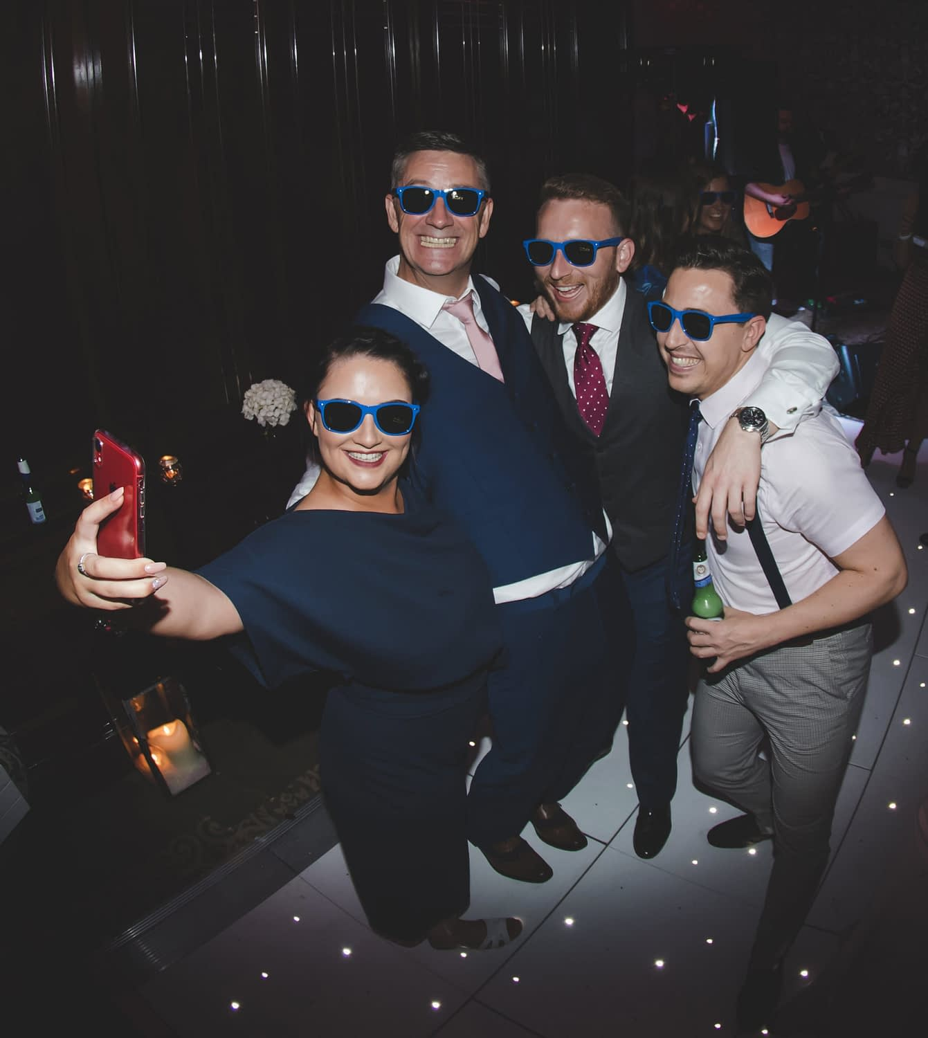 group of four wearing sunglasses indoors taking a selfie