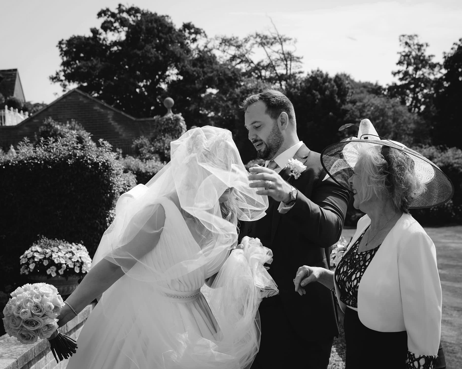 wind blows bride's veil over her face
