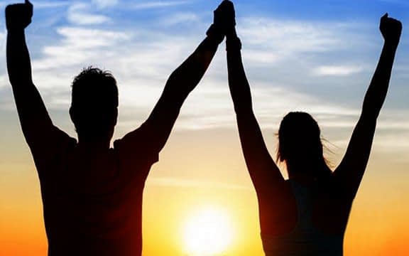 man and woman facing sunset with arm is the air