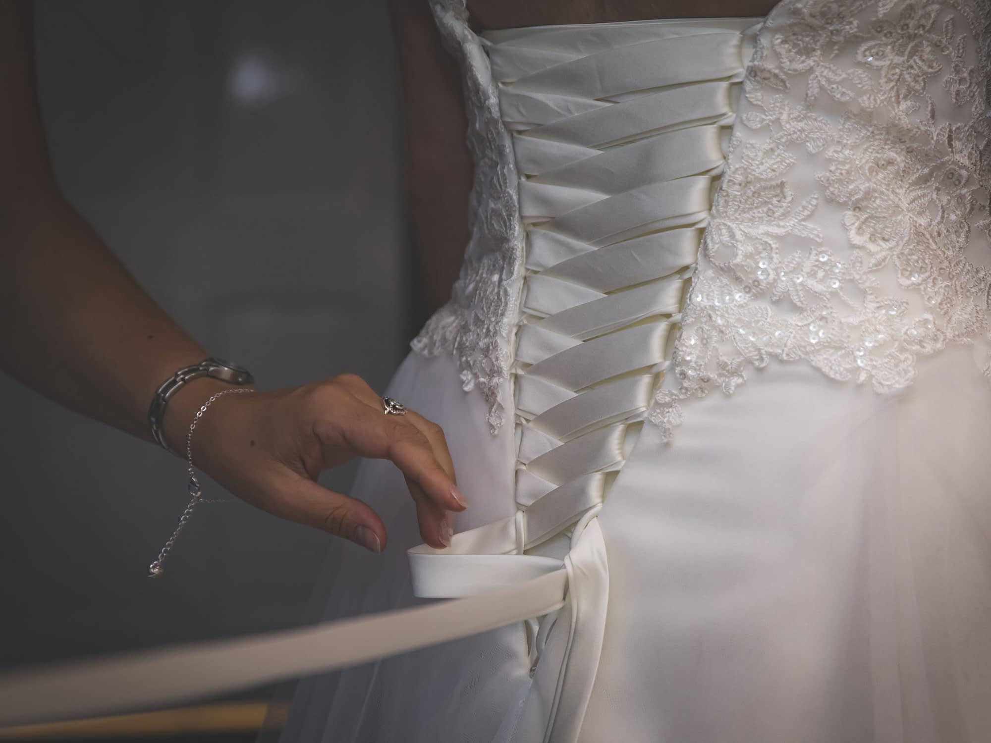 close up of bridal dress being fastened