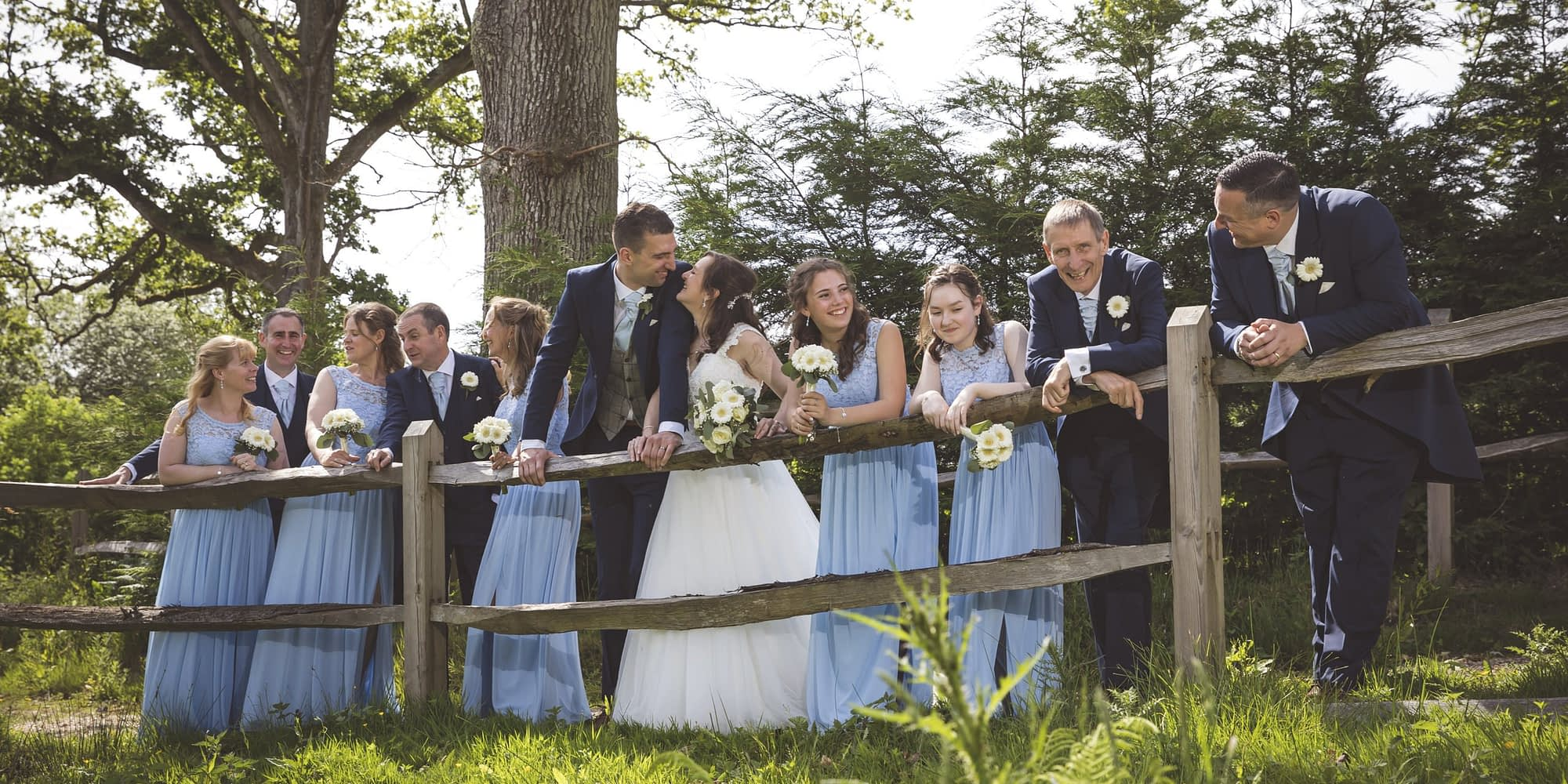 bridal party leaving on a wooden fence talking
