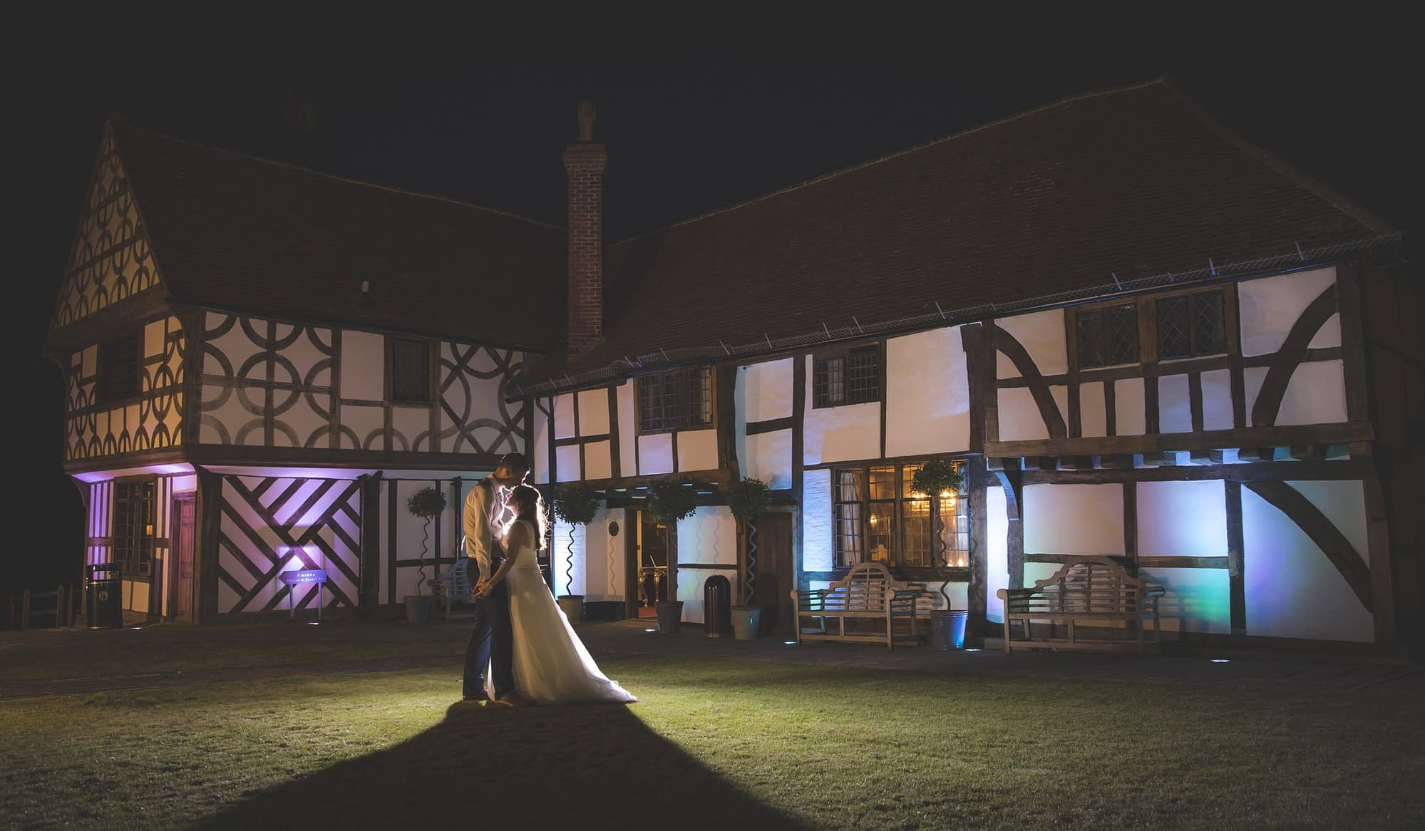 couple standing together outside at night in front of Tudor building