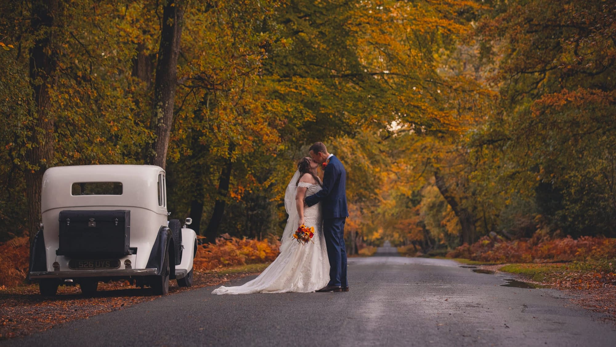 couple kissing in road with trees