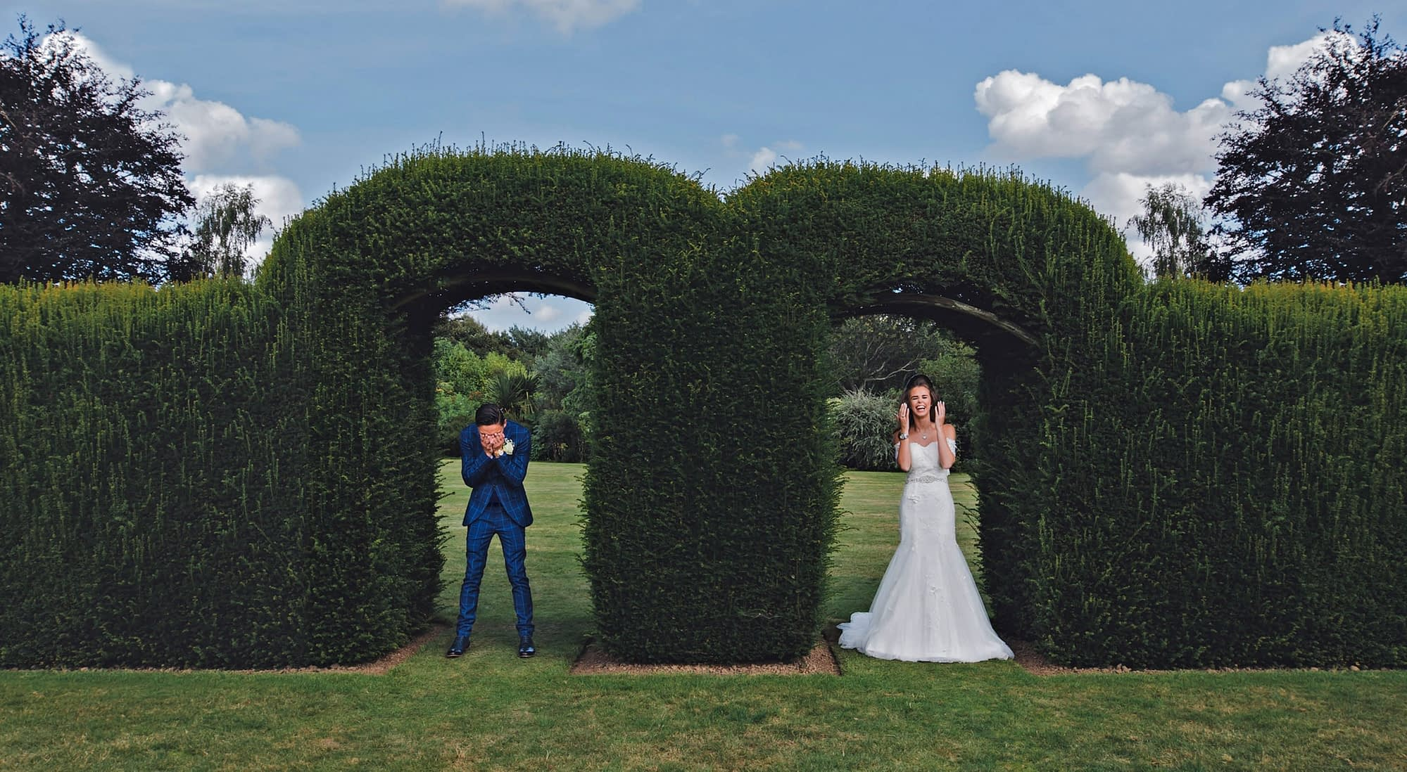 wedding couple laughing in front of a hedge