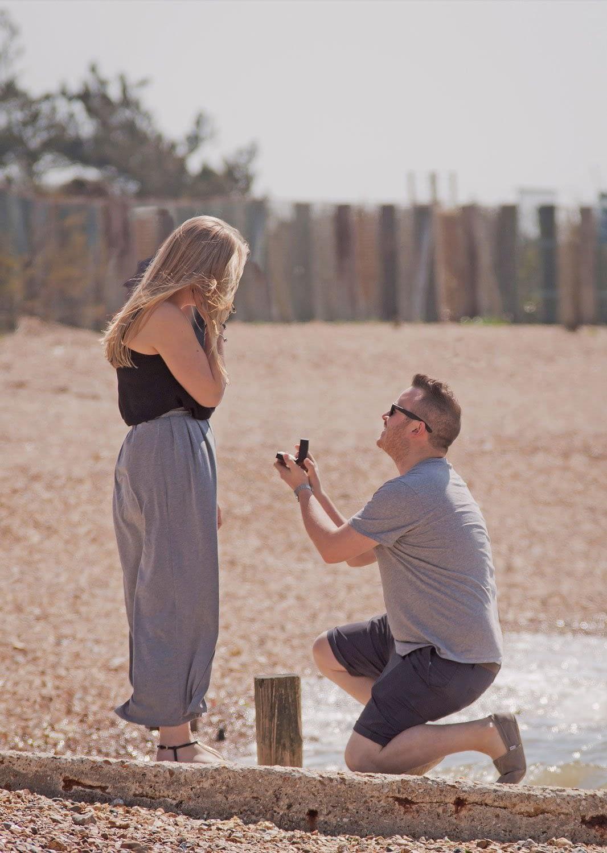 man on bending knee proposing on a beach