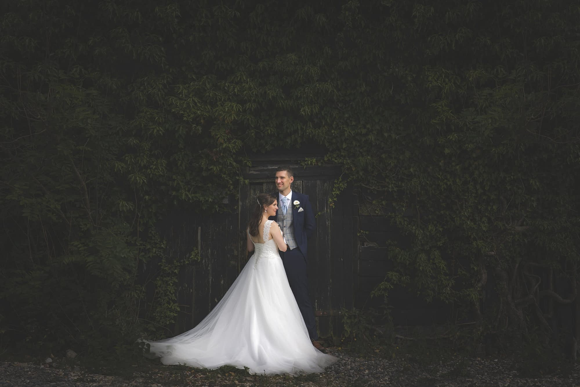 couple standing together in front of green bush