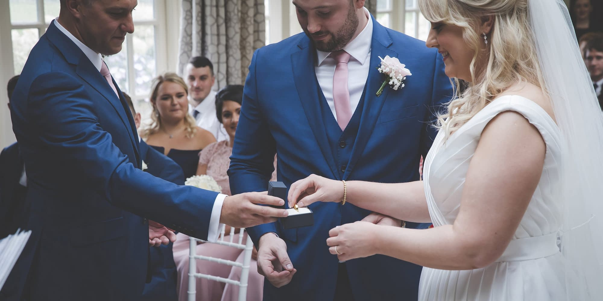 bride takes groom's ring from best man