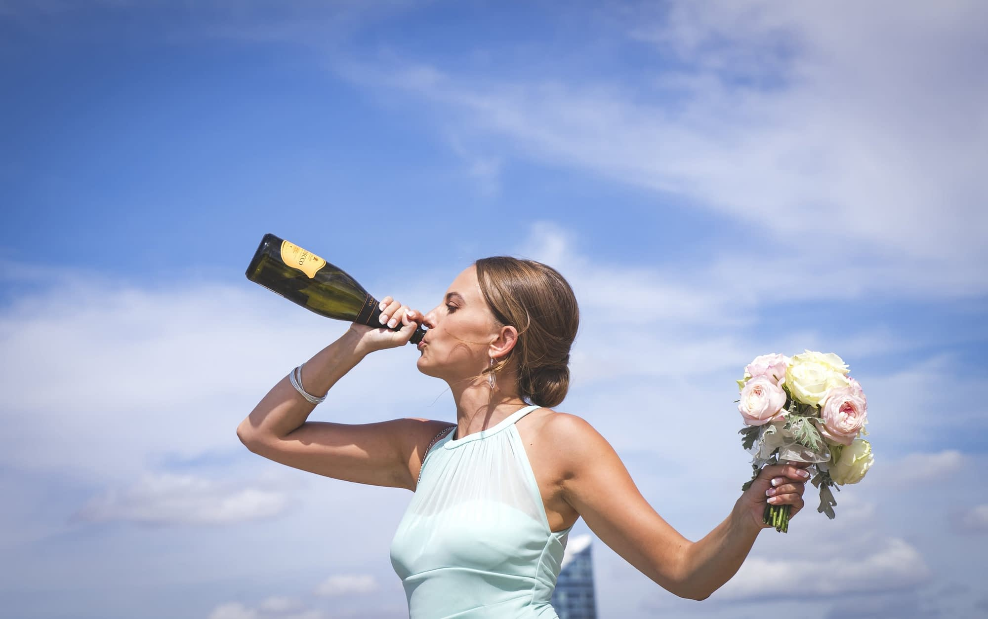 bridesmaid swigging from bottle holding bouquet