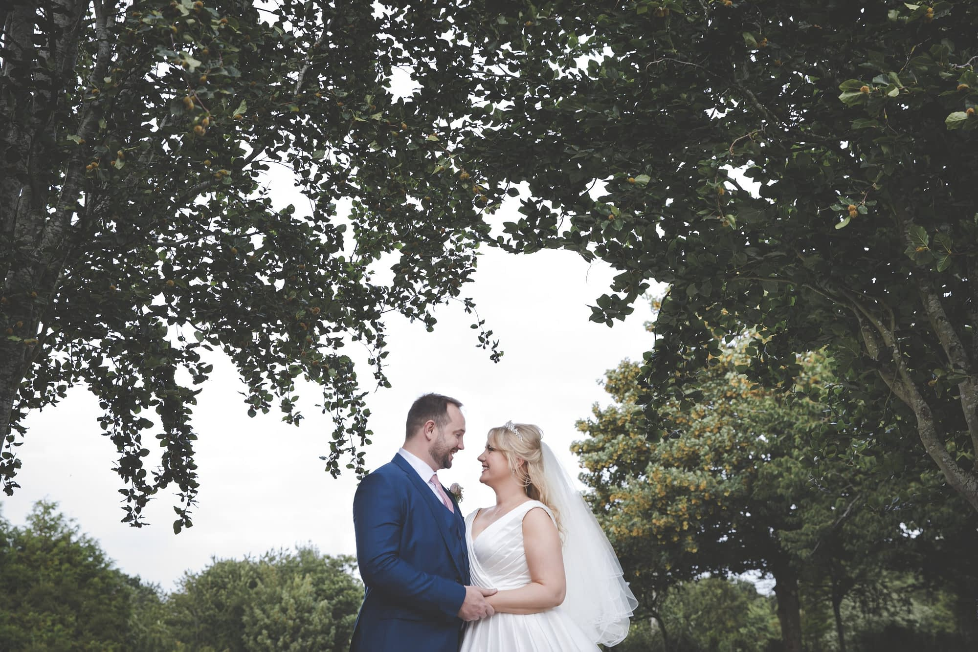 bride and groom looking at each other outside under trees