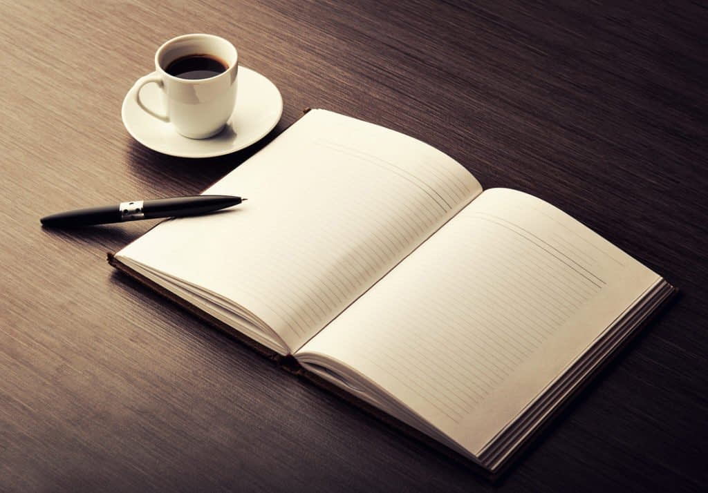 notepad on table with pen and coffee