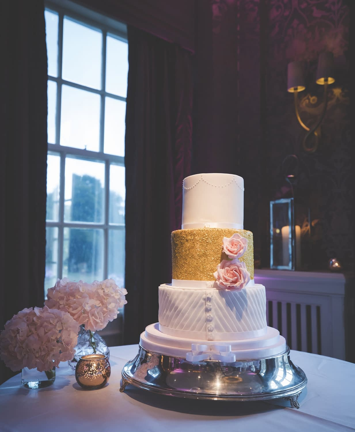 tiered wedding cake and flowers on a table by a window