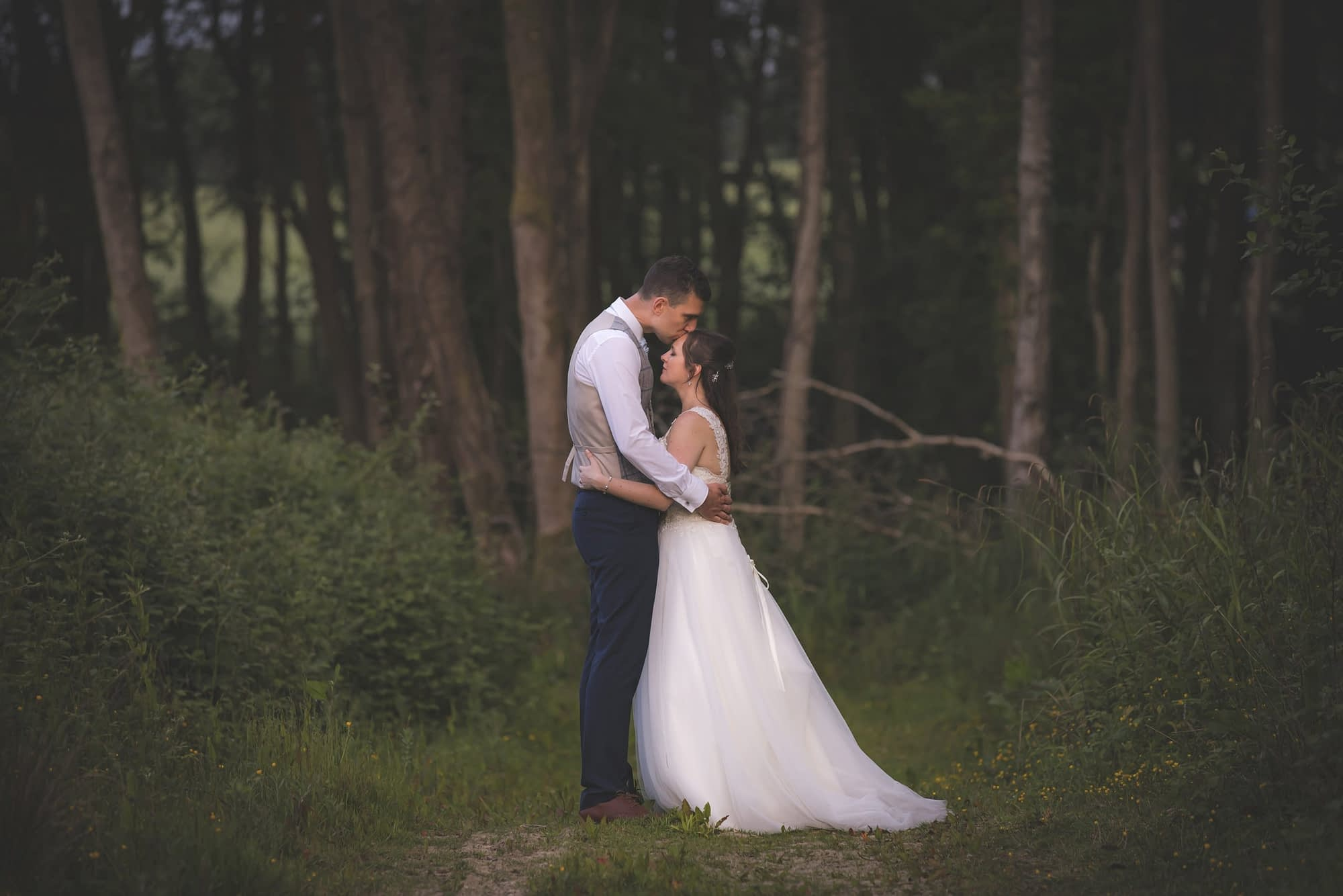 couple standing together outside in a forest clearing