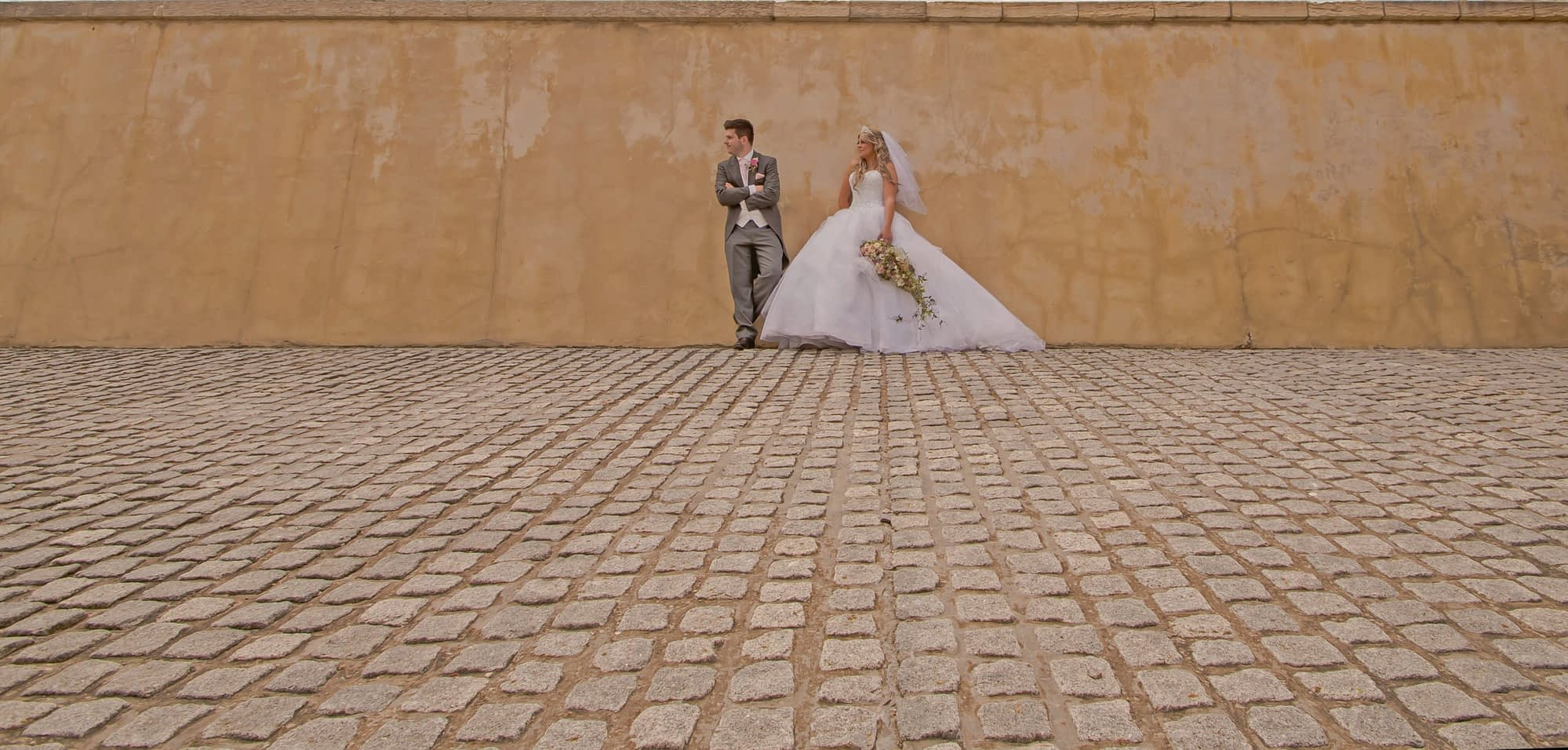 couple outside leaning against yellow stone wall