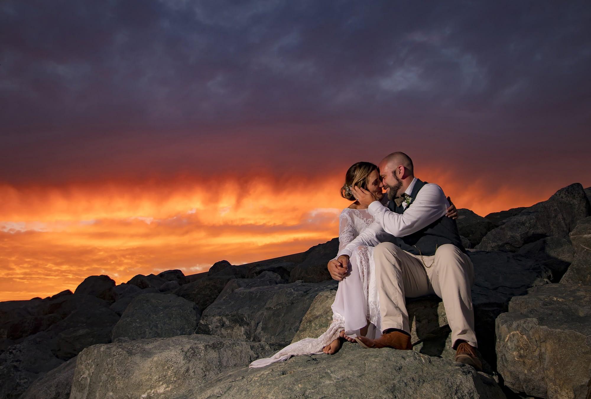 couple sitting on rocks kissing with orange sky