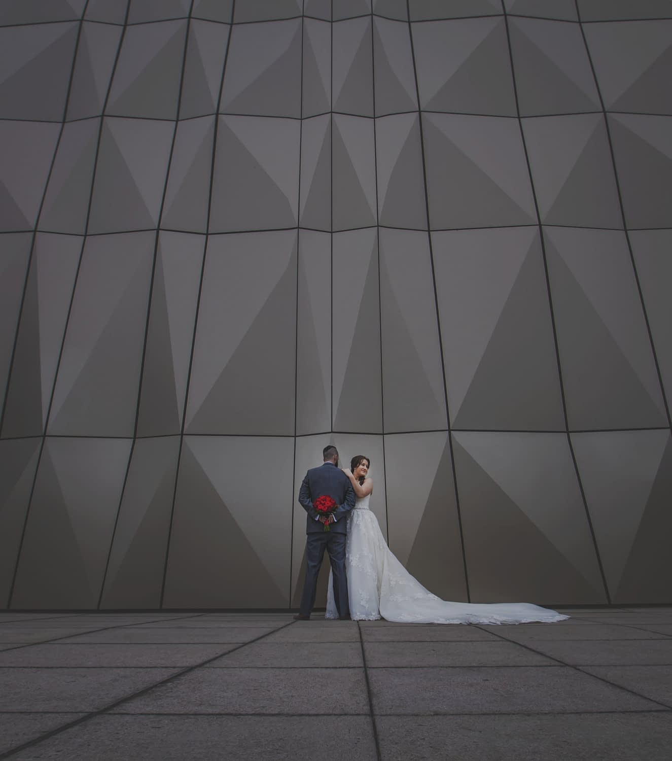 couple standing in front of geometric patterned building