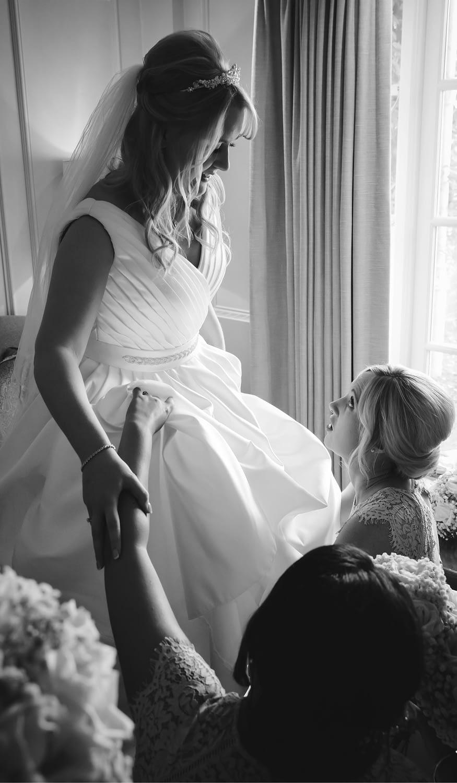 bridesmaid helping bride with garter